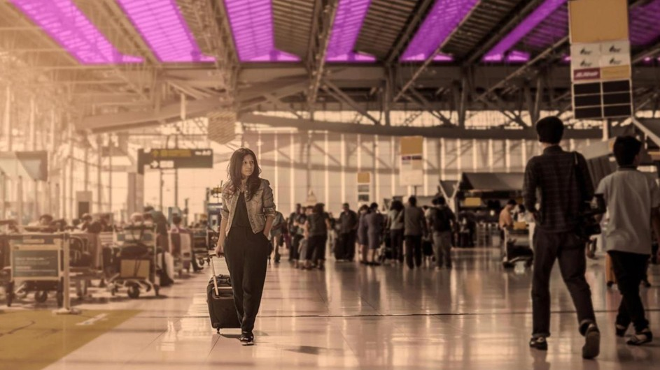 An almost sepia-tone long shot of a woman in pants and a jacket pulling a suitcase through an airport terminal with purple rows of lighting hanging overhead