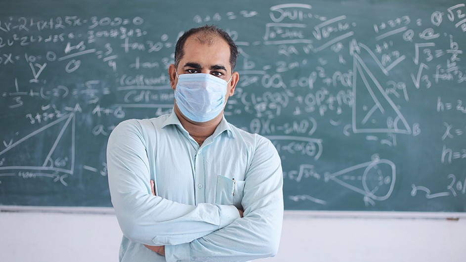 A balding man wearing a blue long-sleeve shirt and a blue surgical mask stands with his arms crossed in front of a blackboard filled with equations.