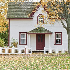 A wood-frame house with red trim and a white picket fence