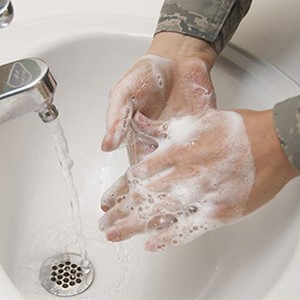 A person washes their hands with soap under a running faucet.