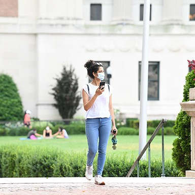A woman walks across campus wearing a mask and holding a cell phone.