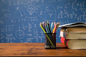 A cup filled with colorful pencils sits next to a stack of books on a desk, a chalkboard filled with equations in the background.
