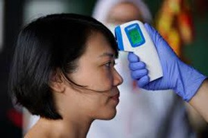 A woman has her temperature taken by someone holding a digital thermometer.