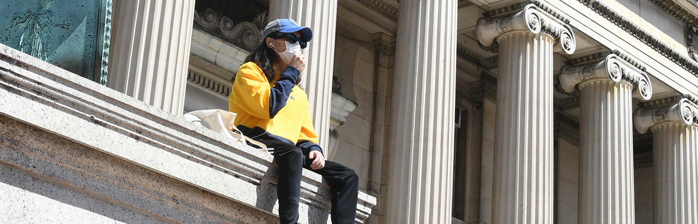 Person in yellow shirt and black pants with baseball hat and sunglasses, wearing surgical mask sitting in front of Columbia University's Low Library, a columned building.