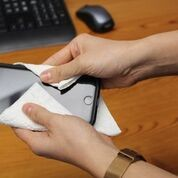Person holds smartphone in a napkin while cleaning on top of a wooden desk while a black keyboard and mouse sits in the background