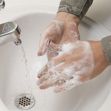 Person lathering soap while washing hands with running water