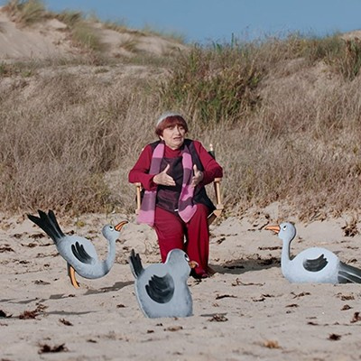 A woman sits on a beach with grassy dunes and  fantasy birds.