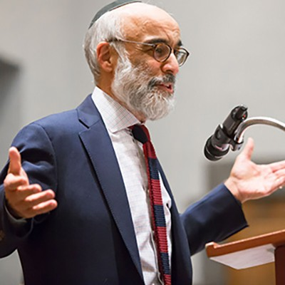 A man in a suit with a beard and glasses lectures before a microphone.